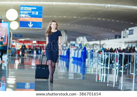 Young woman in international airport, walking with her luggage, back view. Flight attendant going to meet her crew - stock photo
