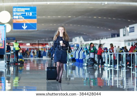 Young woman in international airport, walking with her luggage with coffee to go - stock photo
