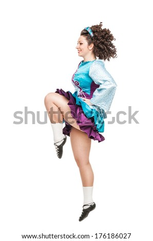 Young woman in irish dance dress dancing isolated