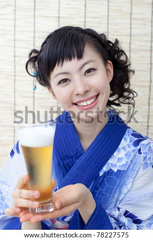 Young woman in Japanese kimono drinking beer