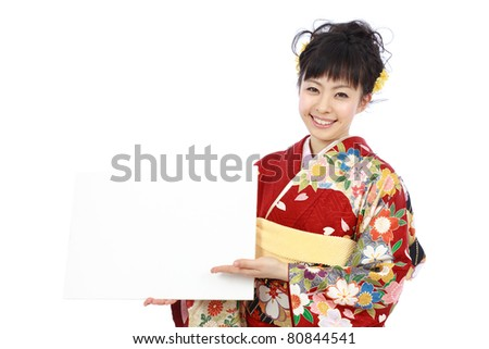 Young woman in Japanese kimono holding blank billboard