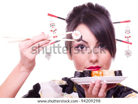 Young woman in Japanese kimono with chopsticks and sushi roll, isolated on white background. - stock photo