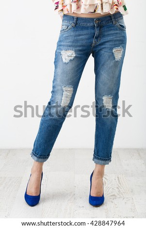 Young woman in jeans and blue suede shoes on white background