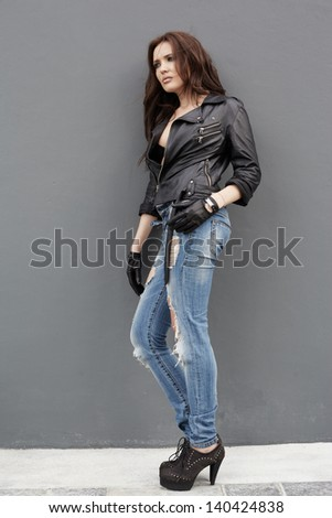 Young woman in jeans and leather jacket near gray wall