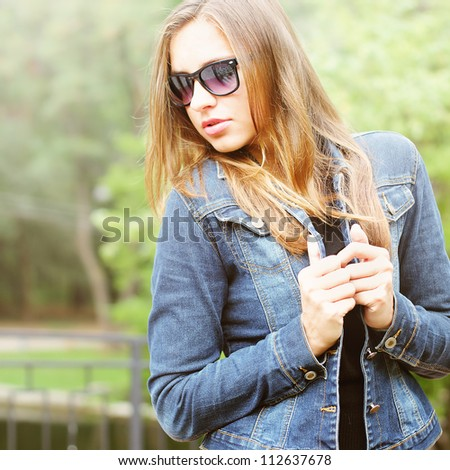 Young woman in jeans jacket walking outdoor - stock photo