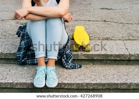 Young woman in jeans, sneakers and t-shirt sitting on the steps next to her yellow skateboard outdoors - stock photo