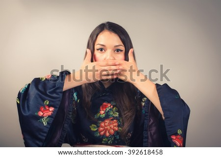 Young woman in kimono covering mouth with her hand - stock photo