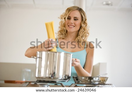 young woman in kitchen cooking spaghetti - stock photo