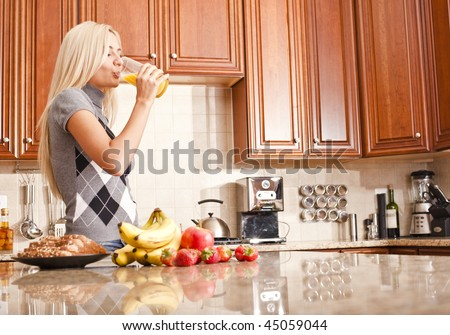 Young woman in kitchen drinking a glass of orange juice. Horizontal shot. - stock photo
