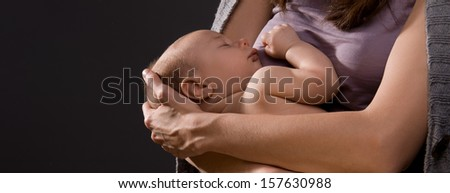young woman in  knitted jacket holding arms of her newborn baby