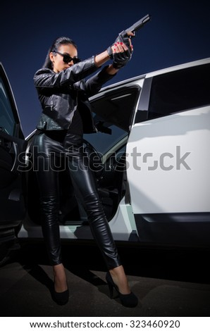Young woman in leather clothes with gun near the car - stock photo