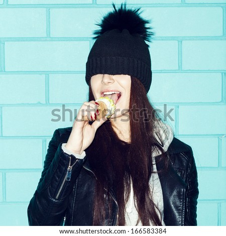 Young woman in leather jacket and hat eating ice cream over blue brick wall. Funky girl having fun. Indoors, lifestyle - stock photo