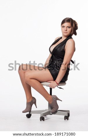 Young woman in leather jacket, miniskirt, high heels, with exceptional haircut sitting on a swivel chair - stock photo