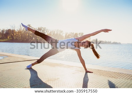 young woman in leggings and white undershirt   on pontoon at lake practice yoga, sunny autumn day, water droplets all around from near by water fountain