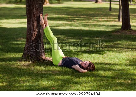 Young woman in leggings on the grass in a cozy position - stock photo