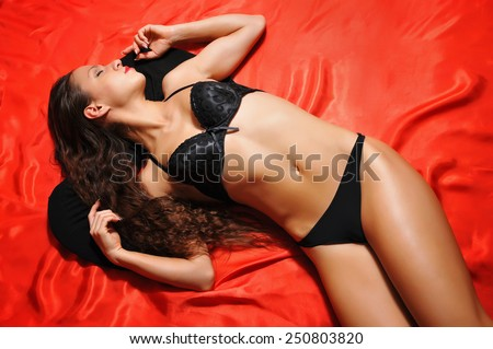 Young woman in lingerie on red bed - stock photo