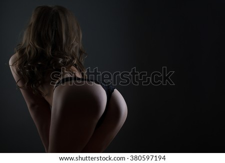 Young woman in lingerie posing back studio shot on dark bg - stock photo