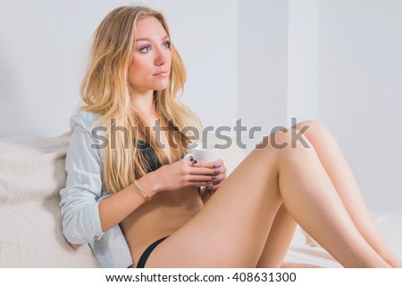 Young woman in lingerie sitting on couch with cup of coffee in the morning, boudoir concept, soft light  - stock photo