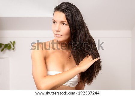 Young woman in lingerie wearing a strapless white bra standing in the bathroom styling her long hair with her fingers after showering in the morning - stock photo