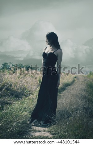 young woman in long black dress stand on rural road summer day full body shot