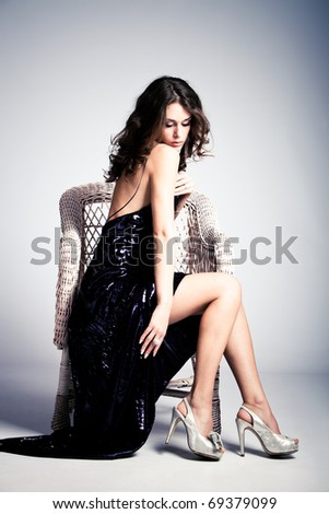 young woman in long elegant dress, sit in arm chair, full body shot, studio shot