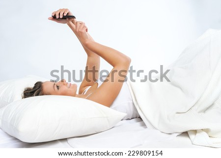 Young woman in looking at mobile phone while lying in bed - stock photo