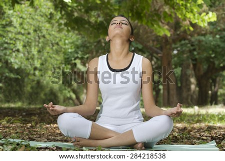 Young woman in lotus position meditating in a park - stock photo