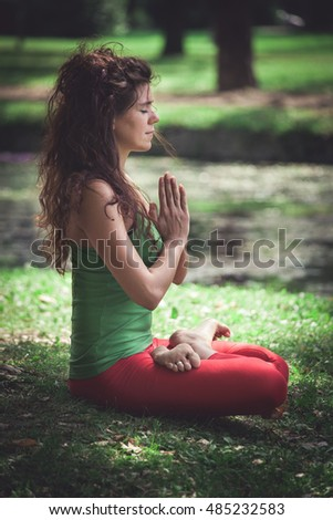 young woman in lotus position outdoor in park side view