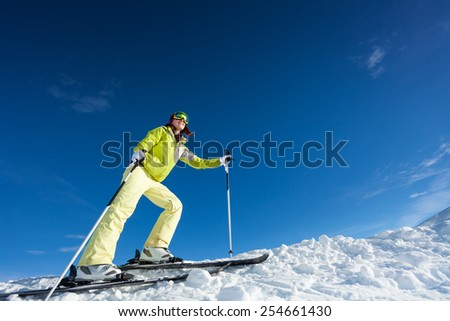 Young woman in mask holding ski poles and skiing - stock photo
