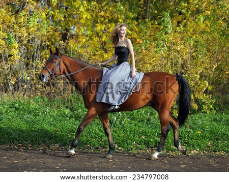 Young woman in medieval dress on horseback