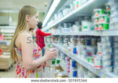 Young woman in milk products department in supermarket