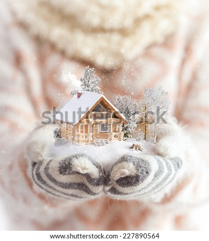 Young woman in mittens holding snow in her hands with a log house. Unusual christmas concept - stock photo
