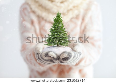 Young woman in mittens holding snow in her hands with snowy tree. Unusual christmas concept - stock photo