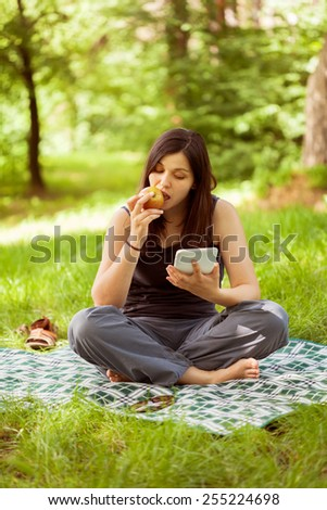 Young woman in nature using digital tablet pc, working in nature  - stock photo