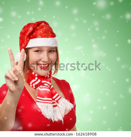 Young woman in new year or christmas suit smiling with victory sign on green background with falling snow
