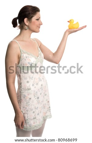 Young woman in night gown holding a rubber duck - stock photo