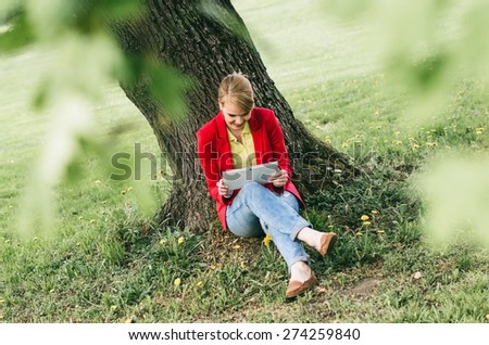 Young woman in office dress code with digital tablet under the tree in a park. - stock photo