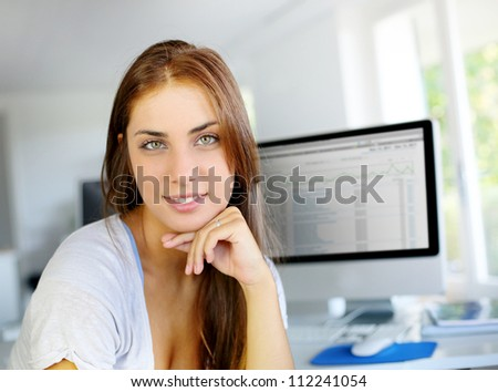 Young woman in office with desktop screen on background - stock photo