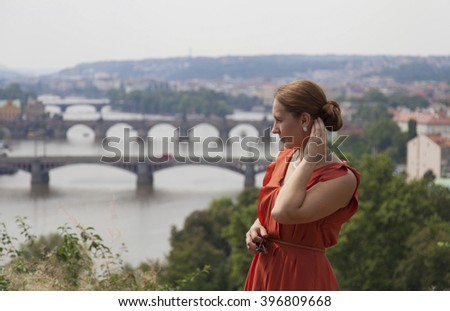 Young woman in orange dress enjoin view of Prague - stock photo
