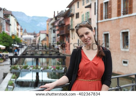 Young woman in orange dress in charming town Annecy, France - stock photo