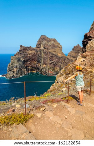 Young woman in orange hat standing on cliff edge and looking at ocean near trekking trail on Punta de Sao Lourenco peninsula, Madeira island, Portugal - stock photo