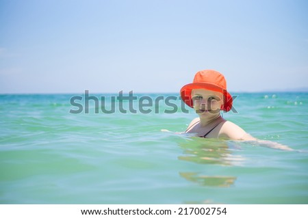 Young woman in orange hat swim in tropical ocean - stock photo