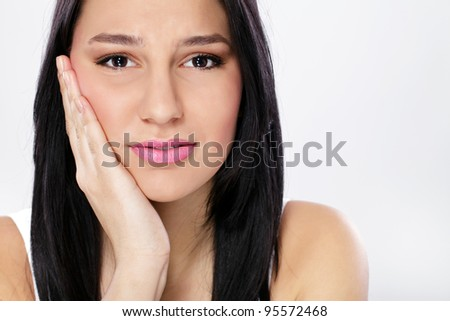 Young woman in pain is having toothache - stock photo