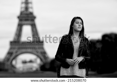 Young woman in Paris, capital of France, waiting for a person anxiously, longing for her lover with room for copyspace, with the iconic Eiffel Tower in the background - stock photo