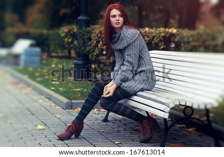 Young woman in park sitting on bench. - stock photo