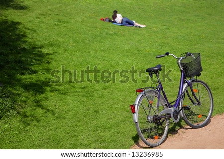 young woman in park with bike - stock photo