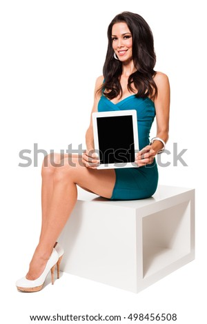 Young woman in party dress showing digital tablet on white