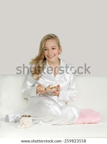 Young woman in payamas with cookies - stock photo
