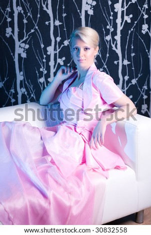 Young woman in pink dress resting on a sofa. Soft blue side light. - stock photo
