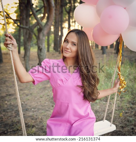 Young woman in pink retro dress is swinging on a swing in summer pine forest. Image toned and noise added. - stock photo